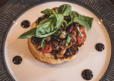 Tomato, basil, black olive and mushroom on a sourdough bruschetta with balsamic oil